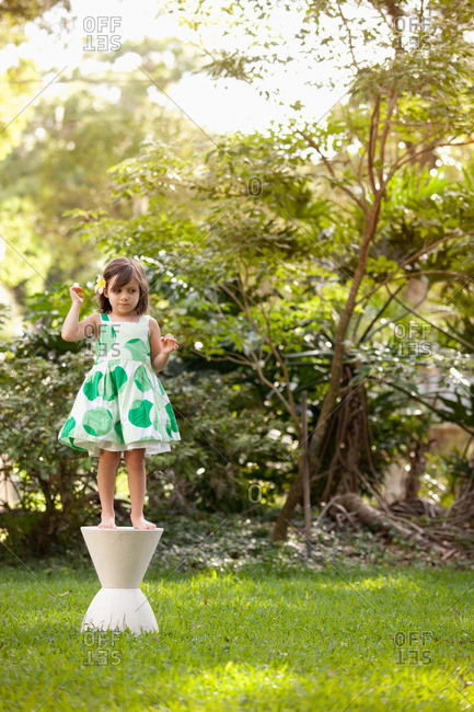 Young girl in garden, standing on pedestal
