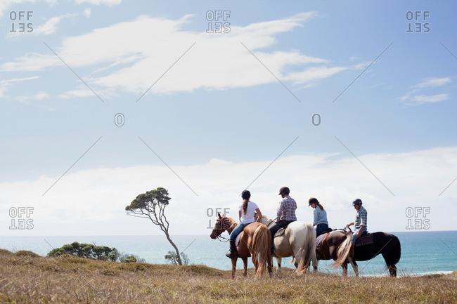 Four horseback riders enjoying the view, Pakiri Beach, Auckland, New Zealand