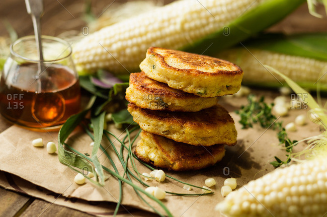 Stack of corn fritters with honey and corn cobs on kitchen table