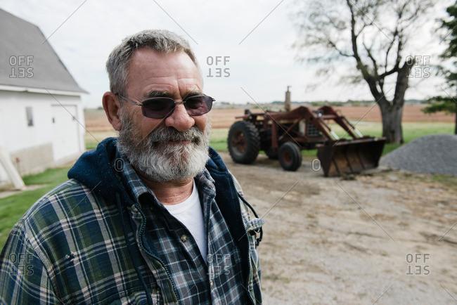 Portrait of senior male farmer in farmyard, Plattsburg, Missouri, USA