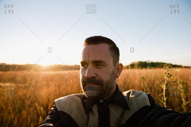 Self portrait of farmer in wheat field at sunset, Plattsburg, Missouri, USA