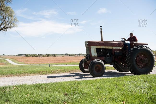Farmer driving tractor on rural road, Missouri, USA