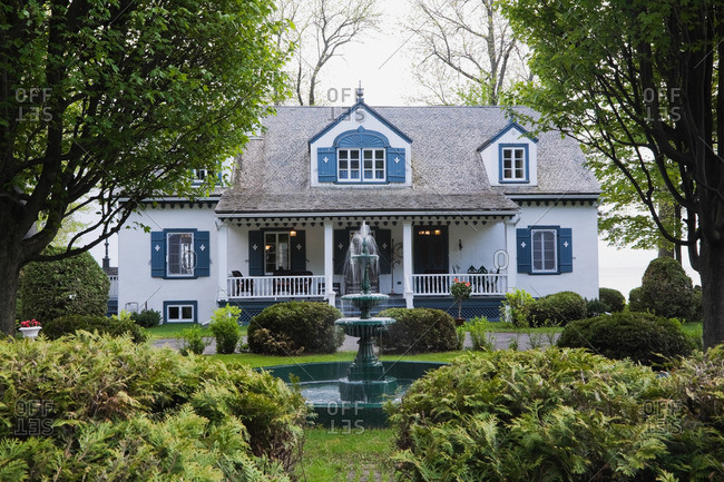 White with blue trim 1920s cottage style house facade with water fountain, Quebec, Canada