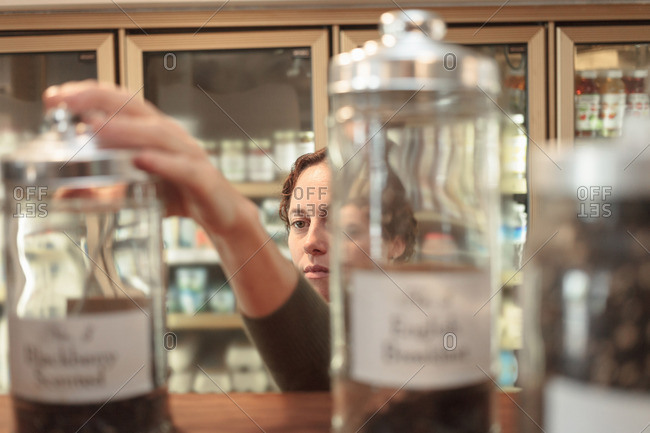 Female customer selecting jar from shelf in country store