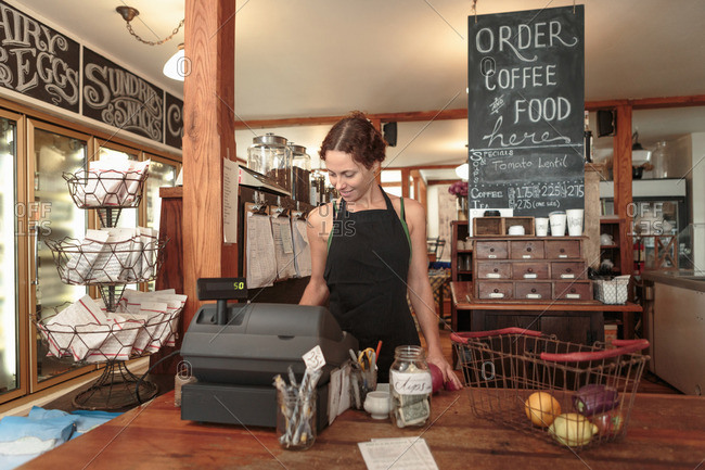 Female sales assistant using check out till in country store cafe