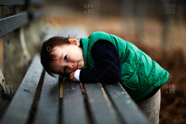 Portrait of male toddler leaning forward on park bench