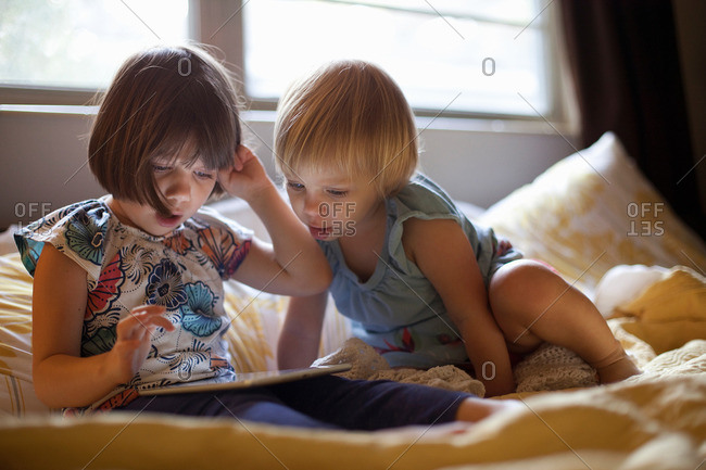 Three young girls sitting on bed using digital tablet