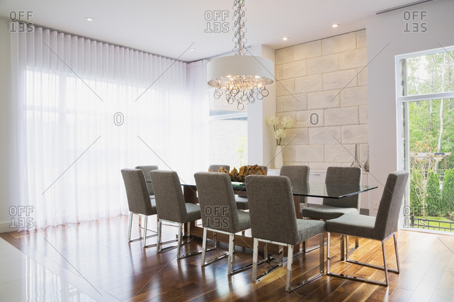 Modern interior design luxury dining room with glass dining table and grey upholstered dining chairs