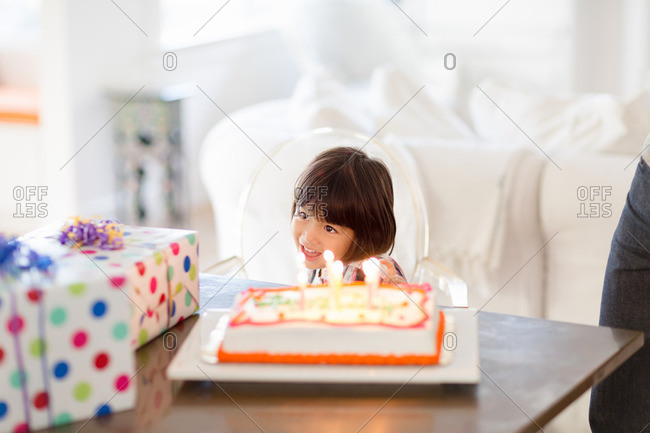 Delighted girl with birthday cake and presents on table