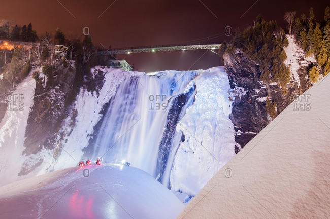 View of snowmobiles in front of frozen Montmorency Falls Park at night, Quebec City, Quebec, Canada