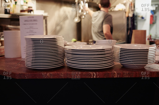 Plates stacked on counter in restaurant, restaurant worker in background