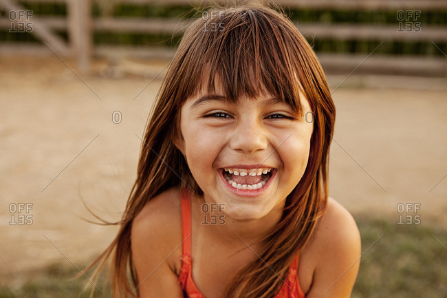 Portrait of laughing girl in farmyard