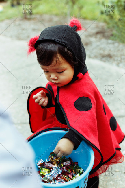 Girl wearing ladybird costume with trick or treat bucket