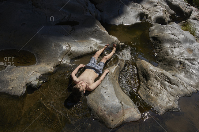 Boy lying on his back in rock pool stream
