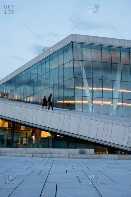 Oslo, Norway - May 1, 2015: A couple walking at the Oslo Opera House at sunset