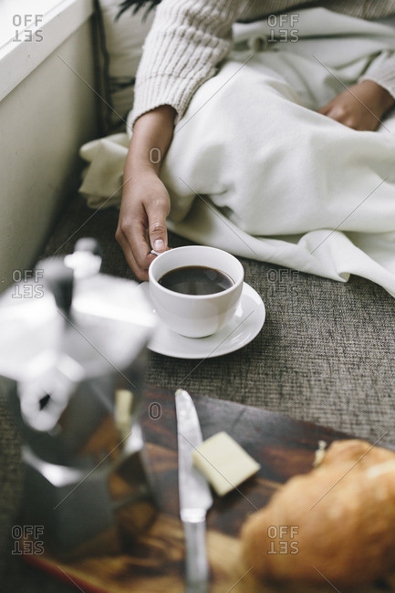 Woman enjoying coffee and croissants on a cushion