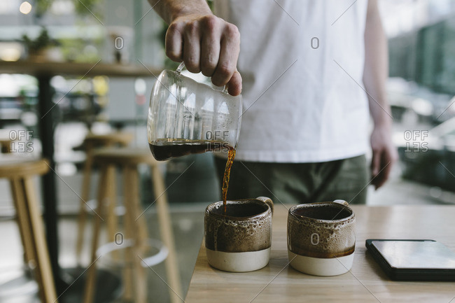 Man pouring coffee into rustic pottery mugs