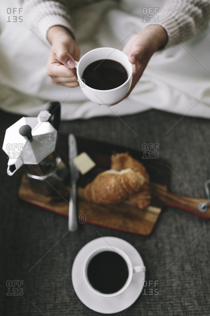 Overhead view of woman holding cup of coffee