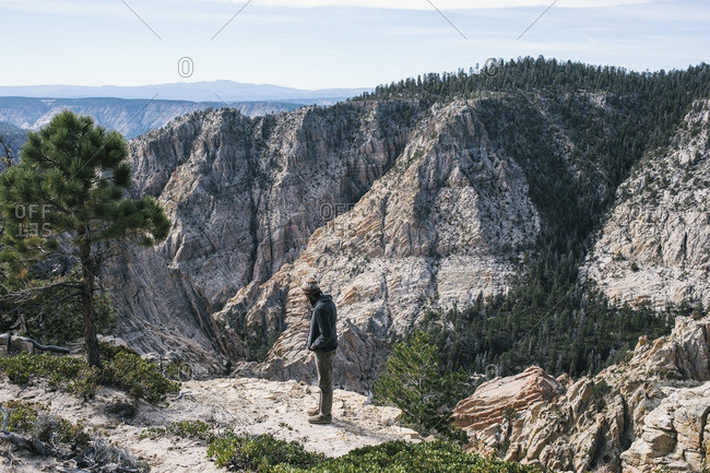 Man standing on ledge in the mountains