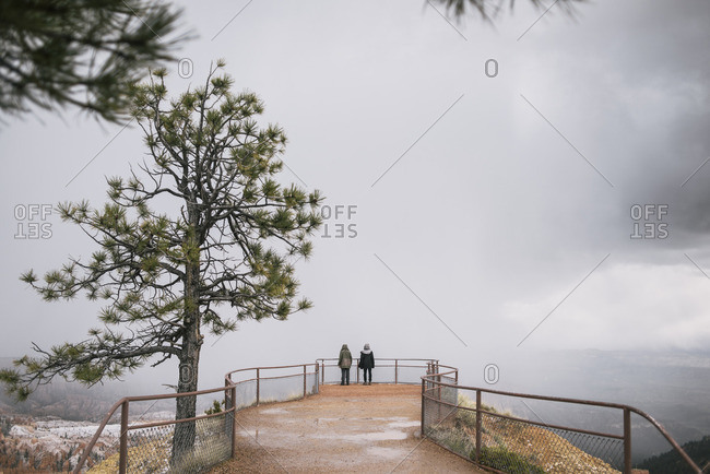 Two people standing on lookout overlooking foggy landscape