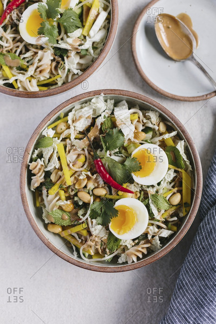 Crunchy pasta and vegetable salad with warm peanut dressing