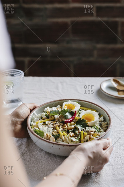 A woman serving pasta and crunchy vegetable salad with warm peanut dressing