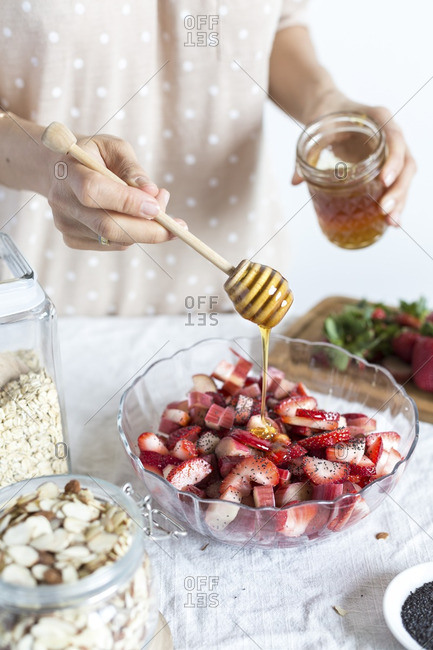 A woman drizzling rhubarb honey over a bowl of strawberries