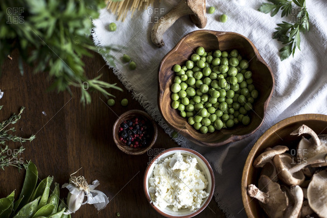 Close-up of ingredients for creamy mushroom pasta with fresh peas, ricotta and shiitake mushrooms