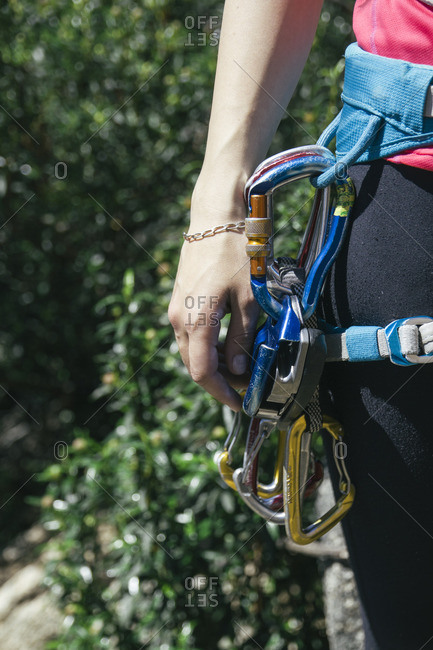 Climbing equipment in the harness of a climber woman