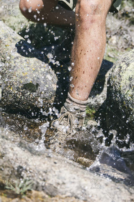 Hiker with a hiking shoe in water splashing