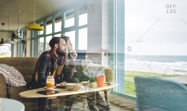 Couple enjoying the seascape through the cafe window while having a brunch