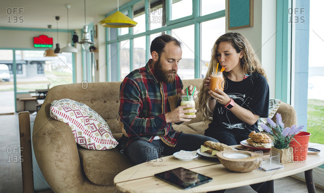 Couple having breakfast in cafe drinking organic juices