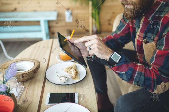 Man sitting in cafe using digital tablet