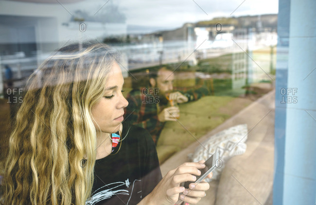 Portrait of blonde woman looking at smart phone in cafe