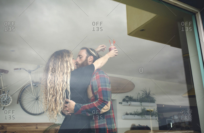 Happy couple embracing in cafe holding fresh juice