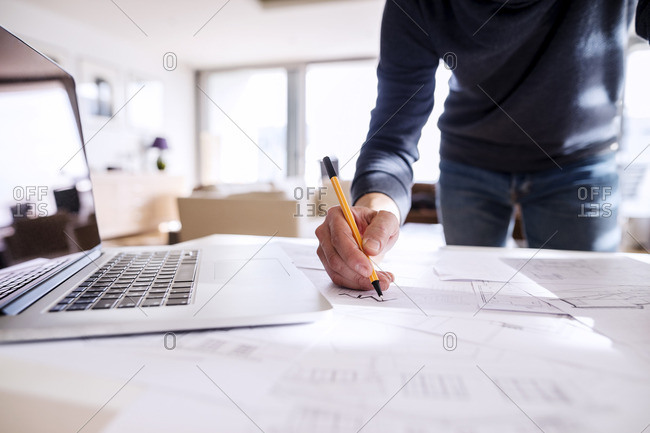 Close up of a man marking architectural plans
