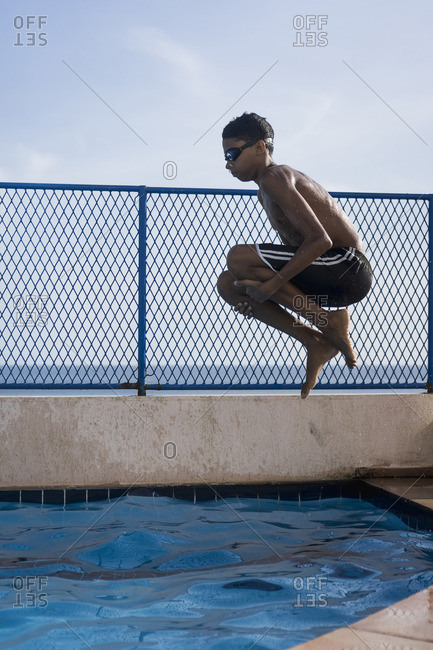 Teenage boy doing a cannonball into swimming pool