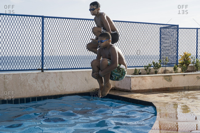 Two boys doing a cannonball dive into swimming pool