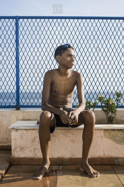 Teenage boy sitting outside swimming pool