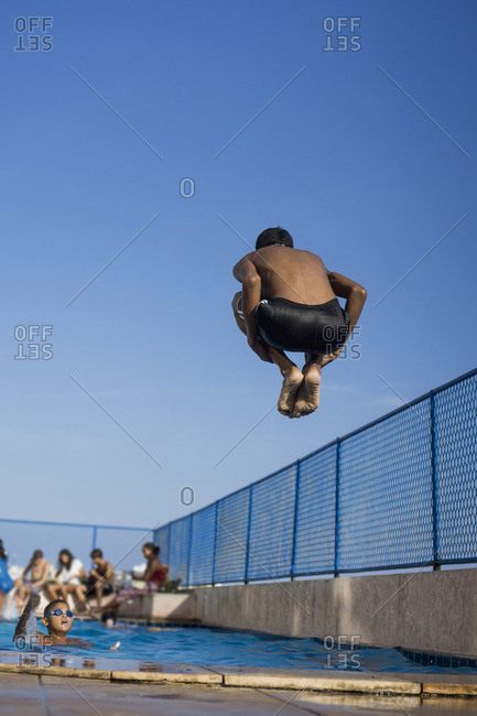 Teenage boy doing a cannonball dive into swimming pool