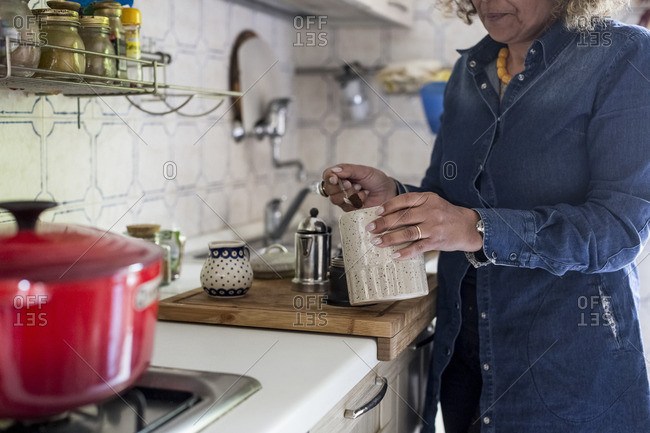 Woman spooning coffee into maker in kitchen