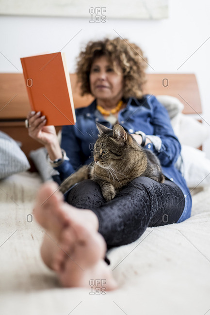 Woman with cat on bed reading book