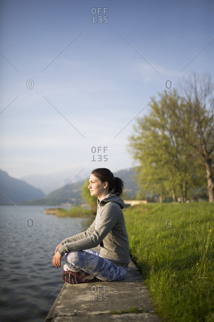 Relaxed young woman sitting at the lakeshore
