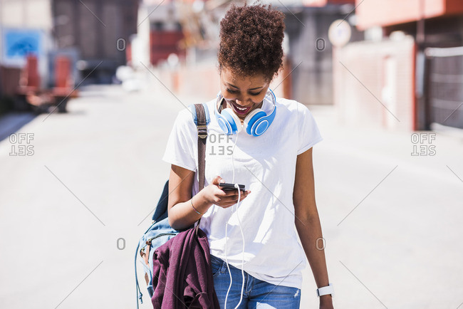 Smiling young woman wearing headphones looking at cell phone outside