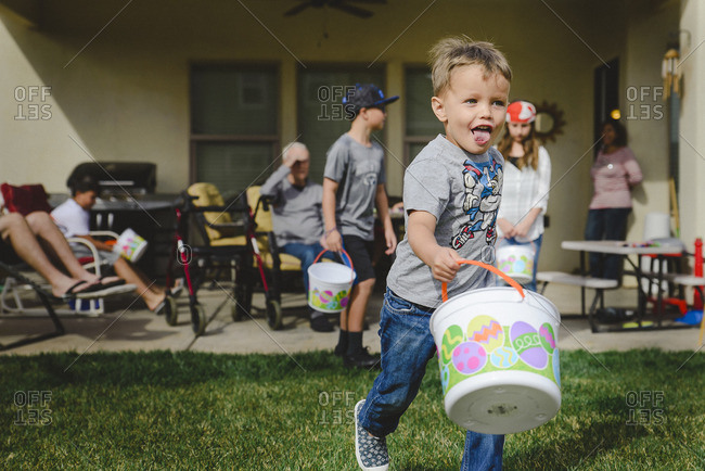 Little boy running with bucket to find Easter eggs