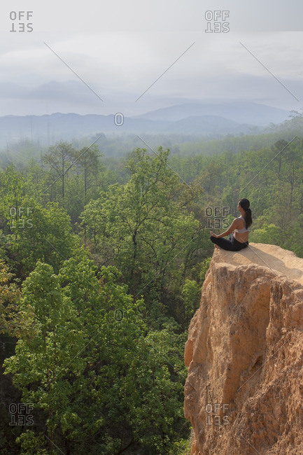Woman meditating in yoga position on an exposed cliff in Thailand