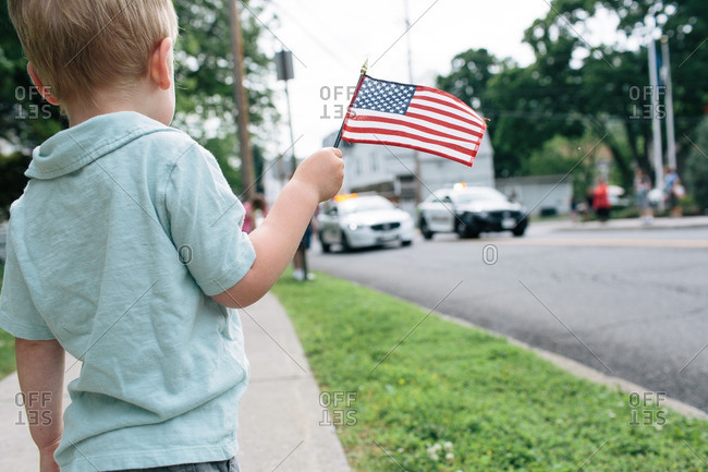 Little boy waving American flag at a parade
