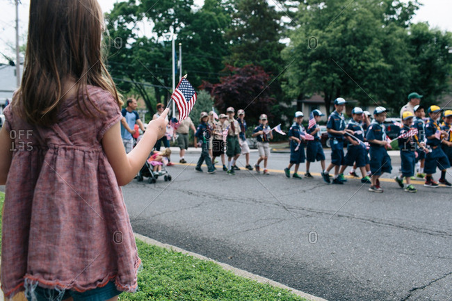 Girl waving American flag at a parade
