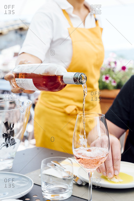 Waitress pouring wine into wineglass