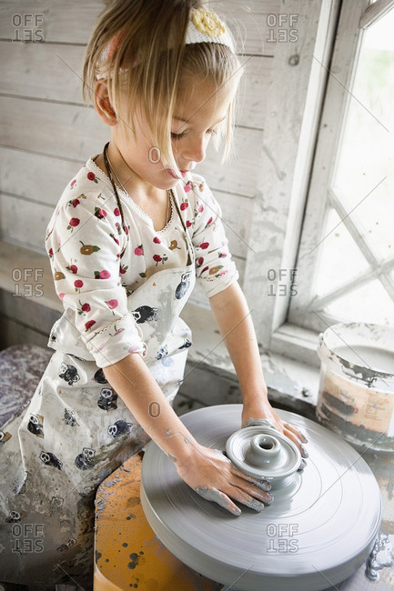 Girl forming pottery on wheel